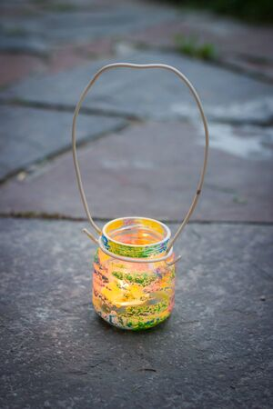Colorful glass jar with metal wire handle candle lamp, kids activities and handmade idea concept
