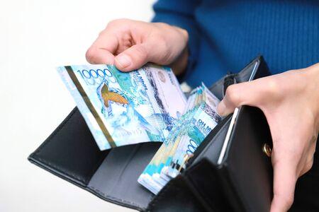 Puts the money in her wallet. Banknote of ten thousand tenge.