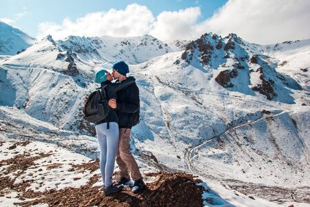 A man kisses a woman in the lips against the backdrop of snowy mountains