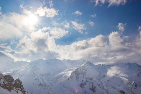 The sun illuminates snow mountain peaks. White clouds. Stockfoto
