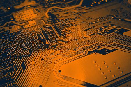 Dark orange electronic mother board circuit close up macro background.