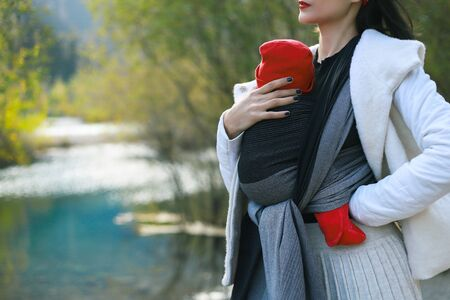 Beautiful young mother with her infant baby in sling outdoor. Mother is carrying her child and travel in autumn mountain lake. Babywearing concept