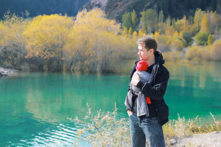 Attractive young father with his infant baby in sling outdoor. Man is carrying her child and travel in autumn mountain lake. Baby wearing concept