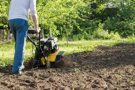 A man during soil plow process by motor cultivator perspective view