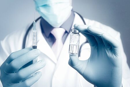 Close up doctor arm using syringe and ampoule, white robe dressed doctor on blurred background. Medical, immunization and vaccination concept