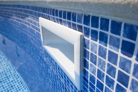 Drain hole in the pool with blue tile. Pool filtration system. Clean water. Фото со стока