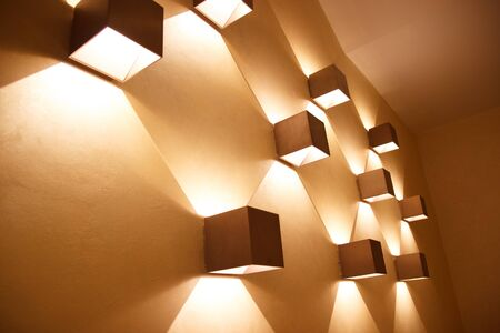 Golden brown bronze color cube shaped sconces on a wall. Geometry in design concept