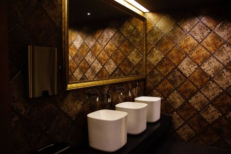 Golden brown design water closet room with bronze color tile on a wall and big mirror three sinks and paper tissue dispenser