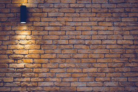 A section of a brown brick wall with an artificial light lamp.