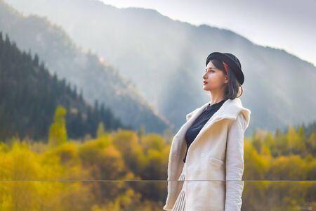 Beautiful woman in a white coat and black hat posing on a background of autumn mountains