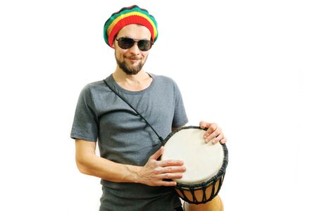 Young caucasian smiling man in rasta hat, sunglasses and grey t-shirt on white background with djembe african drum