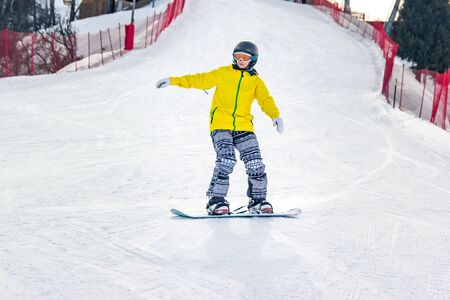 Beautiful young woman in a black helmet and yellow jacket practices snowboarding