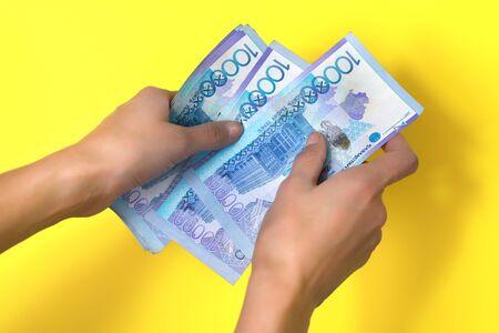 Ten thousand tenge in women 's hands. Yellow background. Stock fotó