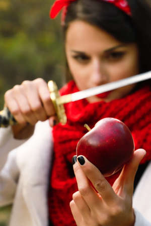 A woman with a sharp blade in her hands is about to cut a red apple.