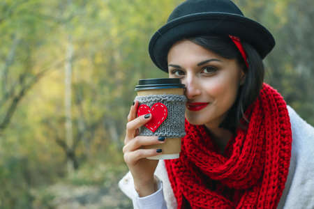 Beautiful young woman in a black hat drinks coffee from cozy cup on the nature. Outdoor picnic good mood