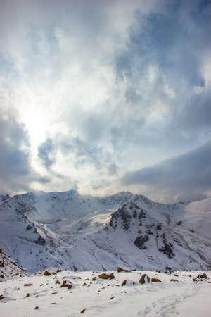 The sun illuminates snow mountains. Clouds close the sky