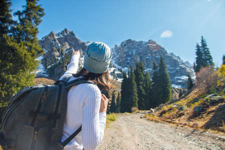 A woman with a backpack points the way. Road in mountainous terrain