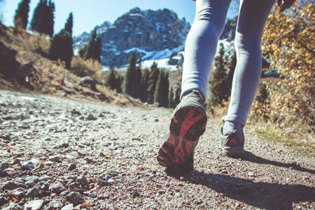 Sports female legs in motion. Sports shoes for hiking in the mountains Archivio Fotografico