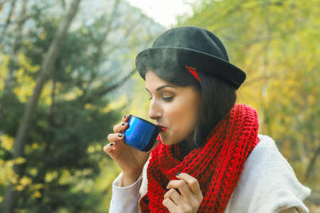 A woman in a white coat, crochet Red scarf and black hat holds a cup in her hands. Tea party in nature