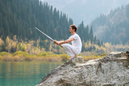 A barefoot man sits on a stone and holds a sword in his hands. Preparing for the battle. Man health concept.