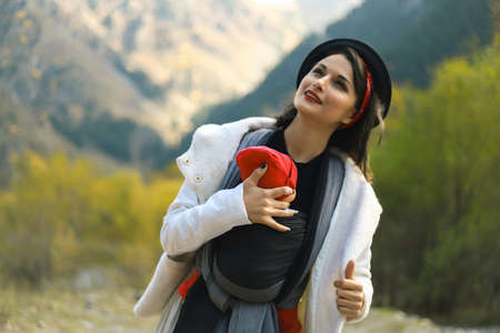 Beautiful young mother with her infant baby in sling outdoor. Woman is carrying her child and travel in autumn mountain. Babywearing concept