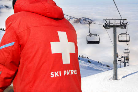 A ski patrol member in a red jacket with a white cross on the back. Ski lift top of mountain