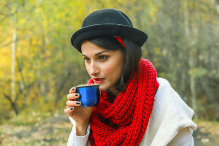 A woman in a white coat, crochet Red scarf and black hat holds a cup in her hands. Tea party in nature.