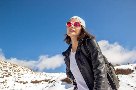 Woman in a leather jacket on a background of a mountain peak. Clouds in the blue sky