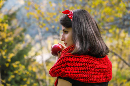 A woman with long black hair is holding a red ripe apple in her hands. Modern red Riding Hood or snow white cosplay. Zdjęcie Seryjne