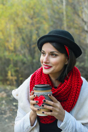 Young woman in a black hat drinks coffee from cozy cup on the nature. Bright smile and good mood. Stok Fotoğraf