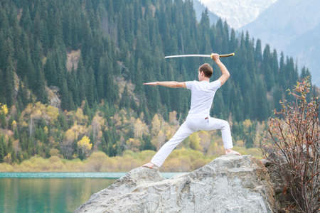A man with a Japanese sword took up a fighting stance. Training in the mountains