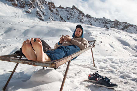A man in winter with barefoot feet is resting on an iron bed in the mountains. Winter vacation fun concept
