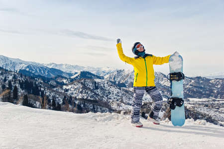 Young woman snowboarder in a yellow jacket and black helmet on the background of snowy mountains.