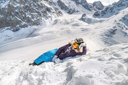 Pretty young woman dressed in winter clothes, glasses and winter funny hat, lying on snow top of the mountain. Winter traveling scene, wanderlust concept.