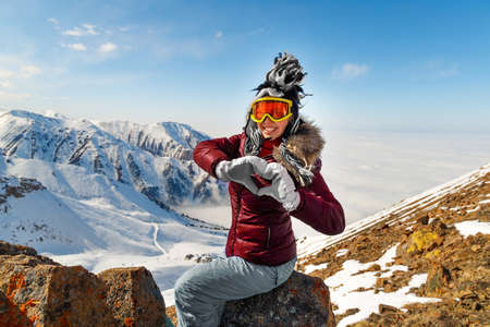 Funny young woman making a heart shape with her hands, sitting over snowy mountain peaks. Winter traveling scene, wanderlust concept. 免版税图像