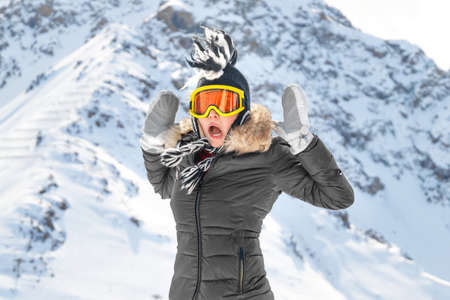 Surprise in the mountains travel. Lifestyle portrait of a cheerful caucasian woman with long curly hair. Traveling in the mountains. Banque d'images