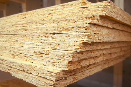 A stack of OSB sheets stacked one on another. Lumber is sold at the supermarket in the warehouse.