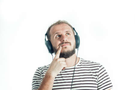 Meditative bearded happy man in a striped T-shirt listens to music with big headphones. 30-35 years old. Isolated