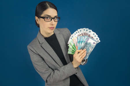 Young beautiful woman in glasses showing a pack of Kazakhstani tenge and Russian rubles in her hand. Selective focus