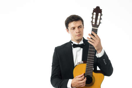 Young man in black classic suit posing with classical guitar and looking at the neck of a classical guitar.