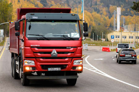 Red Chinese dump truck CNHTC Howo Sinotruk driving down the Almaty street Editorial