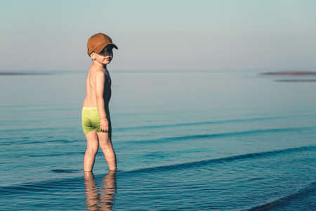 Boy in green shorts and brown baseball cap stands in the sea. Copy space. Toned minimalism photo