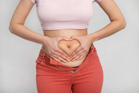 Love your body positive woman. Cropped studio shot of a woman holding her hands in a shape of heart on her fatty stomach