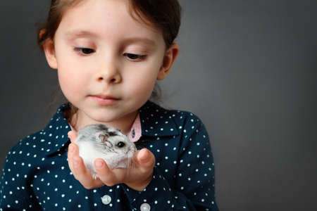 Little cute girl holding and look at her hamster in palms. Selective soft focus.