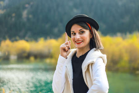 A young woman in a white coat walking in nature, look at camera, index finger up. Stock fotó