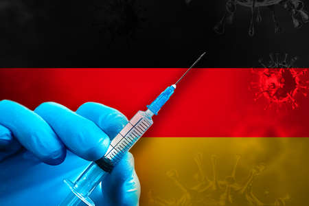 A hand in a blue rubber glove holds a syringe with virus vaccine in front of Germany flag.