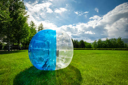 Zorbing Balloon on the summer lawn. inflatable zorb ball outdoor. Leisure activity concept with copy space.