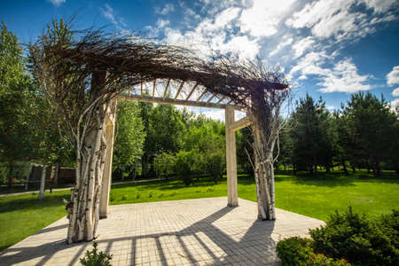 Pergola in a garden with fresh lawn around. Patio place.