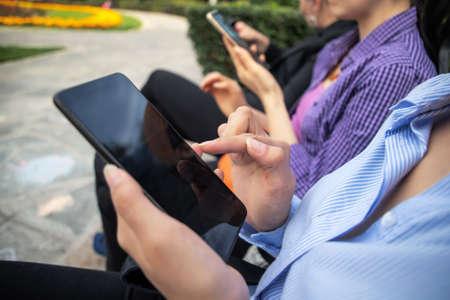 Womans hands using smartphone outdoor in the park Standard-Bild