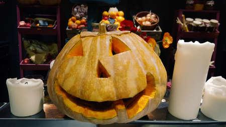 Standard symbol of Halloween, Jack lantern. Smiling head of pumpkin on the shop window.